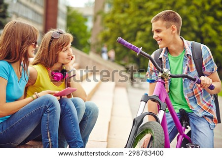 Active guy on bicycle talking to his friends in urban environment - stock photo