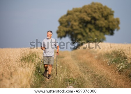 Active handsome senior man nordic walking outdoors on a forest path, enjoying his retirement - stock photo