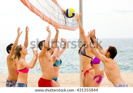 Active happy adults throwing ball on a sandy summer beach near blue sea - stock photo