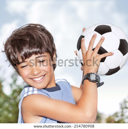 Active happy boy in motion, having fun outdoor, playing football in sportive summer camp, catching ball, best goalkeeper in football team - stock photo