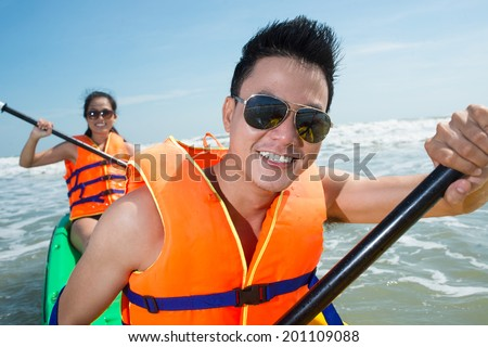 Active happy couple kayaking in the sea - stock photo