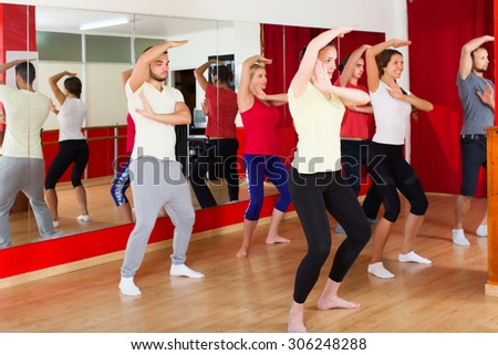 Active happy couples dancing modern style dance in class - stock photo