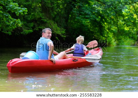 Active happy family, a father with son, teenage school boy, having fun together enjoying adventurous experience kayaking on the river on a sunny day during summer vacation - stock photo