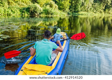 Active happy family. Back view of father with his son having fun together enjoying adventurous experience kayaking on the river on a sunny day during summer vacation - stock photo