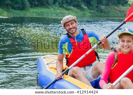 Active happy family. Father with his daughter having fun together enjoying adventurous experience kayaking on the river on a sunny day during summer vacation