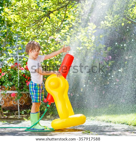 Active happy little kid boy  playing and splashing with a garden hose on hot and sunny summer day. Child having fun with sprinkler outdoors. Funny outdoors leisure wth water for children.