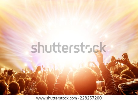 Active happy people enjoying rock concert, many lights from the stage where playing famous musical band, night entertainment concept - stock photo