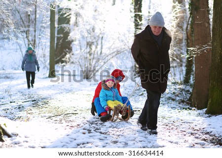 Active healthy grandparents and their happy grandchildren, toddler girl and teenage boy wearing colorful snowsuits enjoying a sledge ride in beautiful snowy forest on sunny winter day - stock photo