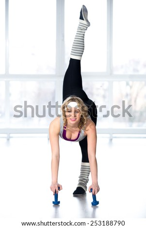Active, healthy lifestyle, hobby, recreation, wellbeing, weight loss concepts. Sporty dancer girl doing stretching exercises for flexibility and balance with dumbbells, warming up - stock photo
