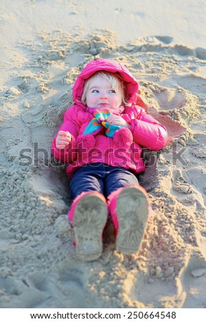 Active healthy little child, laughing cute toddler girl wearing warm pink coat and pretty shoes playing with sand on the beach of North Sea on sunny winter or spring day - stock photo