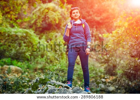 Active healthy woman hiking in beautiful forest. Portrait of happy smiling young woman resting of forest clearing during hike holidays. - stock photo