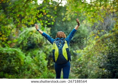Active healthy woman hiking in beautiful forest. Portrait of happy  young woman resting of forest clearing during hike holidays. - stock photo