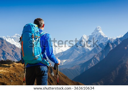 Active hiker hiking, enjoying the view, looking at mountain Himalaya landscape. mountaineering sport lifestyle concept. Ama Dablam mountain view - stock photo