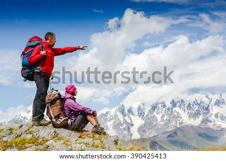 active hikers hiking enjoying view looking at mountain landscape