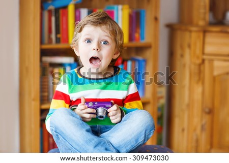 Active kid boy having fun with making photos with photocamera, indoors. Child wearing colorful shirt. Portrait in a daycare. - stock photo