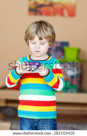 Active kid boy making photos with photo camera, indoors. Child wearing colorful shirt. Portrait in a daycare. - stock photo
