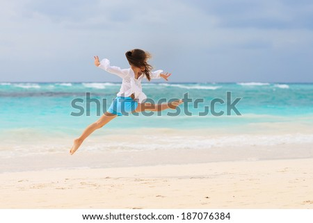Active kid girl jumping on tropical beach on summer vacation