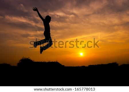 Active kid in silhouette jumps during sunset.