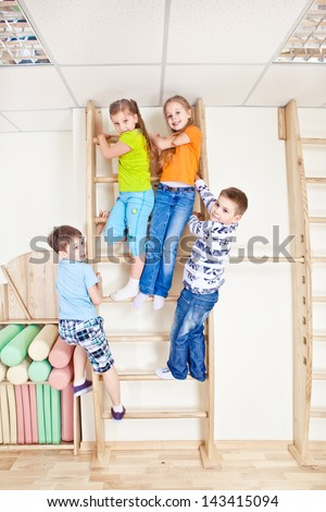 Active kids climbing on the wooden wall bars
