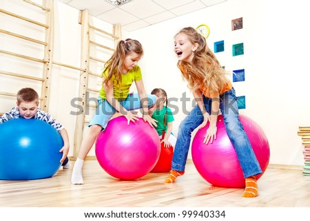 Active kids jump on gymnastic balls - stock photo