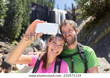 Active lifestyle couple of hikers hiking at Yosemite National Park taking a self-portrait picture with smartphone by waterfall, Vernal Fall. Young hiking couple relaxing in summer nature landscape. - stock photo