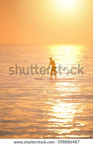 Active lifestyle girl exercising sup board, sunset on background