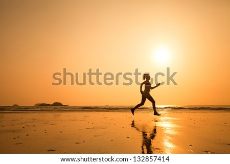 active lifestyle, run to purpose, woman silhouette on the beach - stock photo