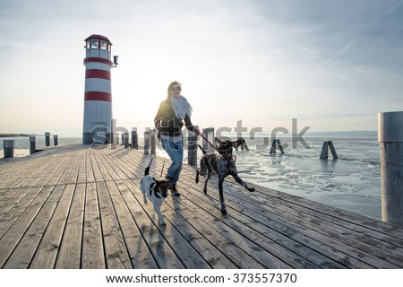 Active lifestyle woman running with two dog outdoor - stock photo