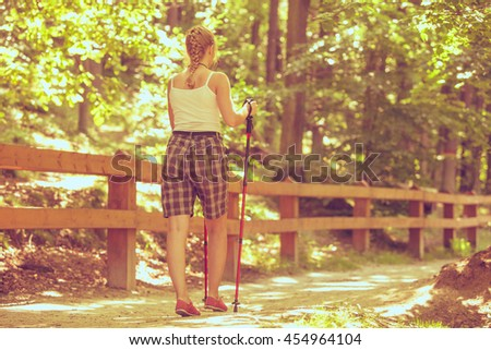 Active lifestyle. Young tourist woman back view hiking in forest pathway - stock photo