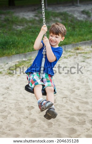 Active little boy hanging on swing rope - stock photo