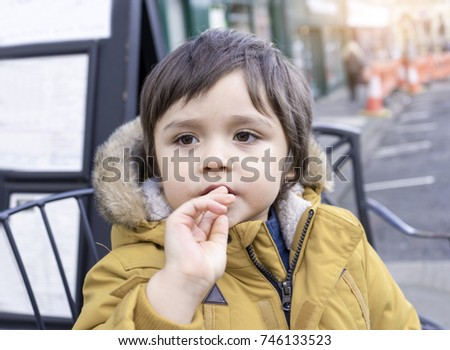 Active little boy putting fingers in his mouth and looking out of the street