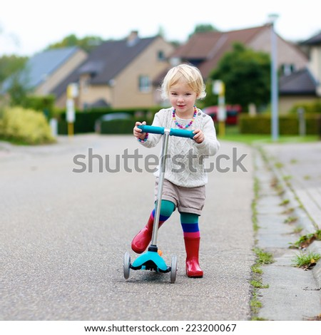 Active little child, cute blonde toddler girl learning to ride and balance on push scooter on the street in the countryside