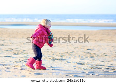 Active little child, laughing cute toddler girl wearing warm pink coat and pretty shoes playing with sand on the beach of North Sea on sunny winter or spring day - stock photo
