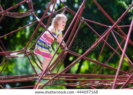 Active little child playing on climbing net and jumping on trampoline at school yard playground. Kids play and climb outdoors on sunny summer day. Cute girl on nest swing at preschool sport center. - stock photo