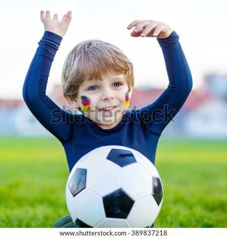 Active little kid boy  having fun with playing soccer with football on field, outdoors. In white German national uniform and painted German flag on face. Happy child about european championship - stock photo