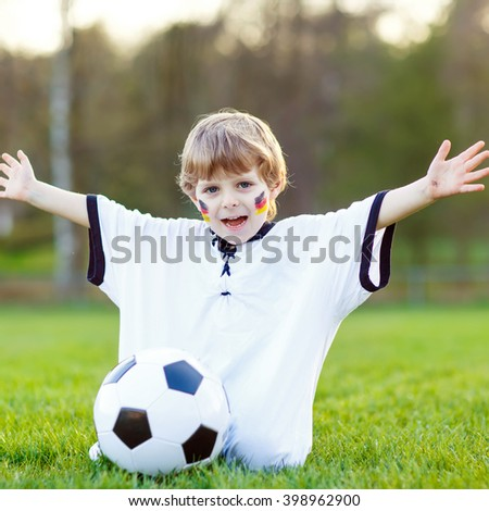 Active little kid boy  having fun with playing soccer with football on field, outdoors. In white German national uniform and painted  flag on face. Happy child about european championship - stock photo