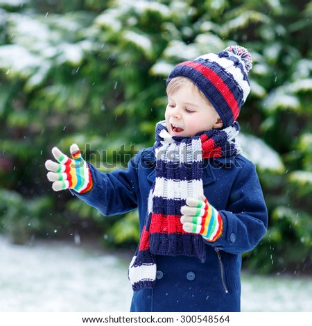 Active little kid boy in colorful winter clothes having fun with snow, catching snowflakes, outdoors during snowfall on cold day. Active outdoors leisure with children in winter. - stock photo