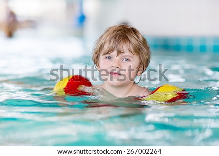 Active little toddler boy with swimmies learning to swim in an indoor pool. Active and fit leisure for children. - stock photo