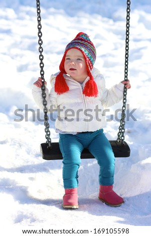 Active little toddler girl has fun in playground on a sunny snowy winter day - stock photo