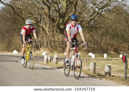 Active male athletes riding bicycles on a country road - stock photo