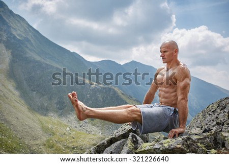 Active man doing exercises in a gorgeous mountain view - stock photo
