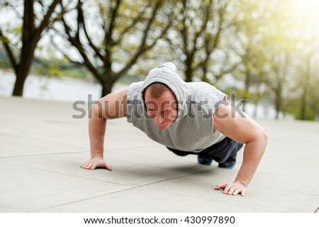 Active man doing push up in park.