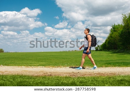 Active man tourist walking on the trail with backpack and water bottle in hand, outdoor