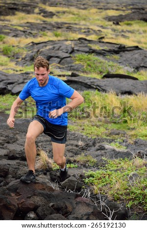 Active man trail running on volcanic rocks in mountain background. Male athlete racing doing an ultra marathon through rugged landscape in Hawaii, USA. - stock photo