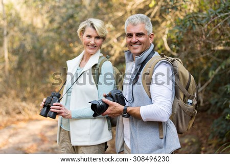 active mature couple in forest looking at the camera - stock photo