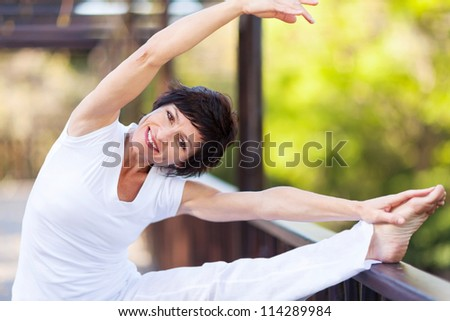 active middle aged woman stretching - stock photo