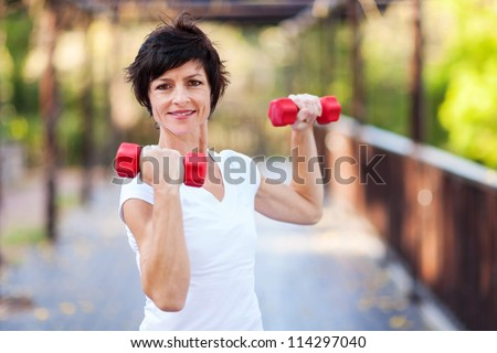active middle aged woman workout with dumbbells - stock photo