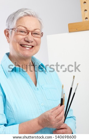 Active old lady with paintbrush and canvas, smiling. - stock photo