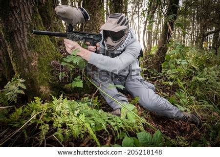 active paintball sport player in the forest with protective clothing - stock photo