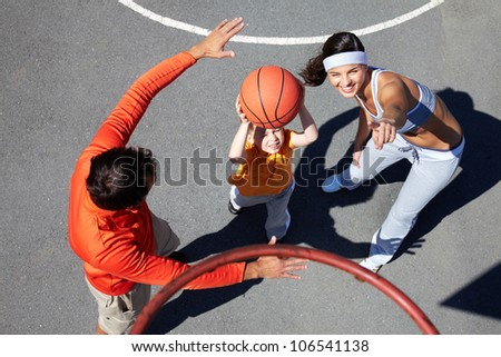 Active parents teaching their son how to play basketball - stock photo
